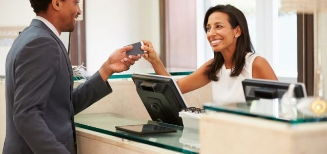 hotel receptionist handing key to guest   functions of a property management system   HiRUM