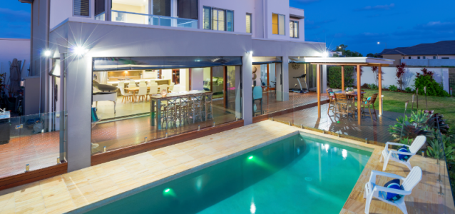 2 storey house at dusk with large pool   maximise your holiday rental income   HiRUM