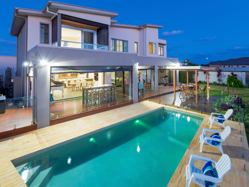 2 storey house at dusk with large pool | maximise your holiday rental income | HiRUM